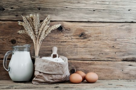 Photo for Paper bag of flour on a wooden table with spikelets of wheat, milk and eggs on wooden background close-up. Free space for text. Copy space - Royalty Free Image