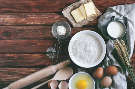 Photo for Ingredients for baking - flour, milk, eggs, butter. View from above. Rustic background with free text space. Ingredients for the dough - Royalty Free Image