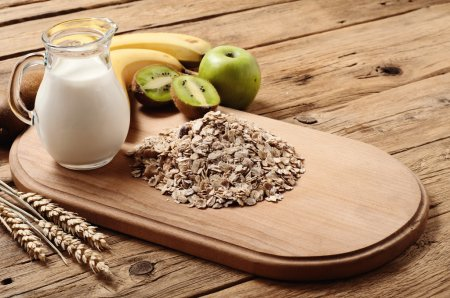 Photo for Oat flakes with fruit (banana, kiwi, apple) and milk on wooden surface. Rustic style - Royalty Free Image