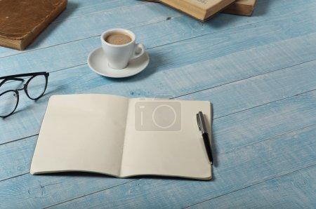 Photo pour Table de bureau à domicile avec carnet ouvert avec pages blanches, une tasse de café expresso et des livres. Vue supérieure avec espace de copie - image libre de droit