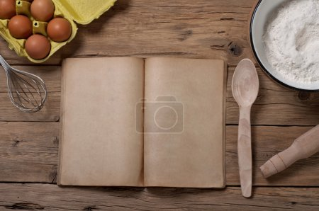Photo for Cookery book with blank pages on the old kitchen table with ingredients for baking. View from above. Free space for text. Copy space - Royalty Free Image