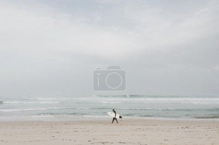 Surfer walking with surfboard