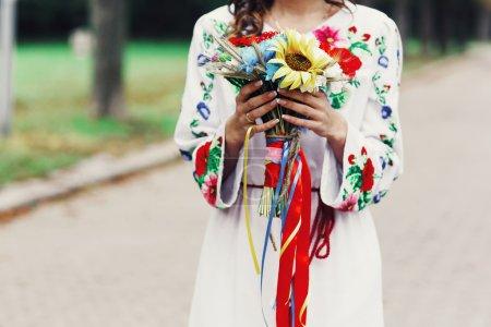 Photo pour Belle mariée brune en vêtements ukrainiens traditionnels posant dans le parc avec bouquet - image libre de droit