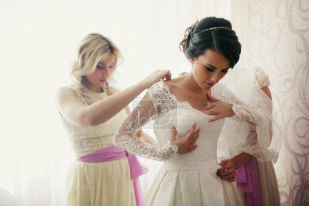Cheerful bridesmaids help bride