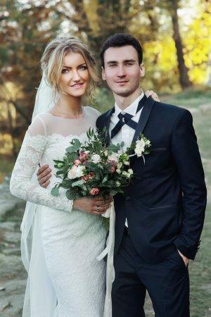 Photo pour Magnifique mariée blonde avec bouquet et beau marié posant près du vieux château - image libre de droit