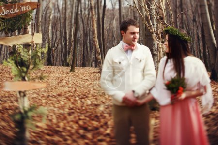 bride and groom in the wedding ceremony in forest near the decor