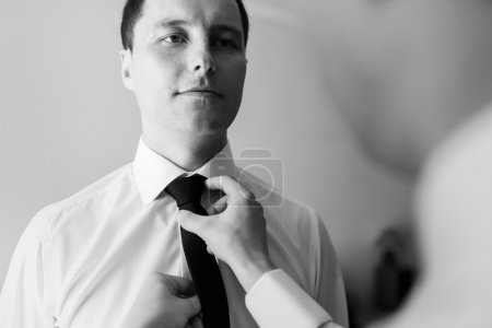 Bridegroom preparing for the wedding, corrects a beautiful balck