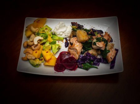 Photo for Healthy food on white plate on dark brown wooden table. Salmon, Potatoes, Beets, Spinach, Mango, Avocado, Cashew nuts, Creme fraiche, Chili flakes. - Royalty Free Image
