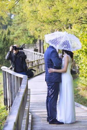 Wedding photographer taking photographs of groom and bride