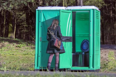 Photo for Girl at a portable toilets at an outdoor in the park. The modern plastic portable toilet has been manufactured since the 1960s. - Royalty Free Image