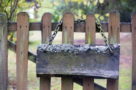 Old mossy signboard with chain on a wooden fence