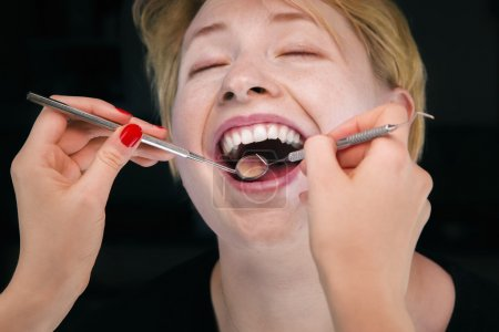 Dentist examine patient's teeth