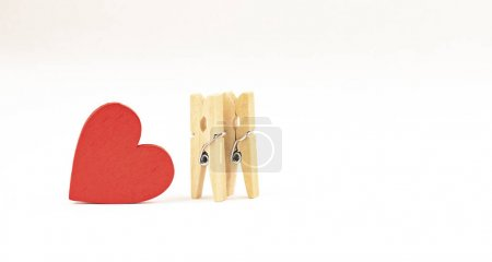 Photo for Concept composition of love relationships outstanding. two clothespins and red wooden heart. - Royalty Free Image