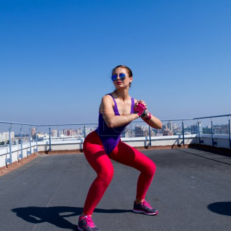 Fitness girl exerting outdoors going jump squat in amazing top city view. Fit female woman athlete cross-training outside. Wearing wearing sportive violet swimsuit,pink leggins and sunglasses.