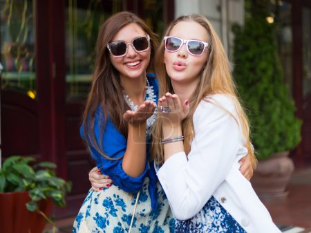 Photo for Close up lifestyle selfie portraits of two young positive woman having fun and talking about secrets, teenage hipster trendy clothes and sunglasses, long hairs,fresh make up. happy together. sisters - Royalty Free Image