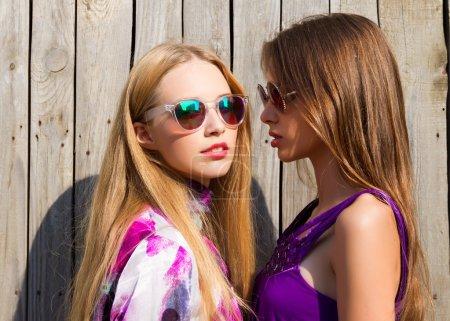 Photo pour Deux vivaces belles jeunes femmes en mode été courte robes posant, portrait en plein air intégral, au fond de mur en bois. Portrait de deux soeurs de hipster jolie vue rapprochée. - image libre de droit