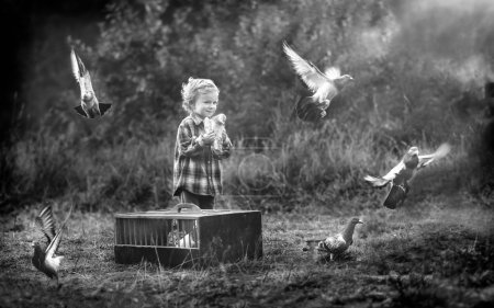 Photo for Little pigeon fancier. Boy playing outdoor in autumn or spring scenery with flying pigeons. - Royalty Free Image