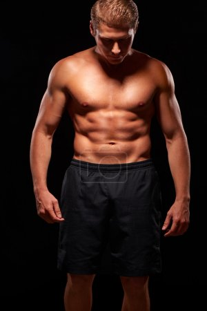 Powerful shirtless muscular man looking down, isolated on black