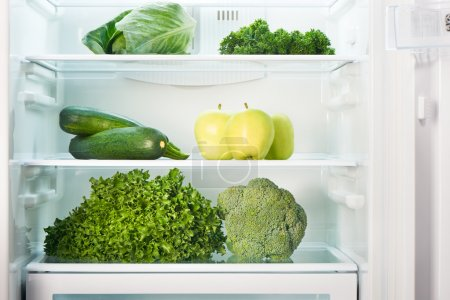 Open refrigerator full of green fruits and vegetables