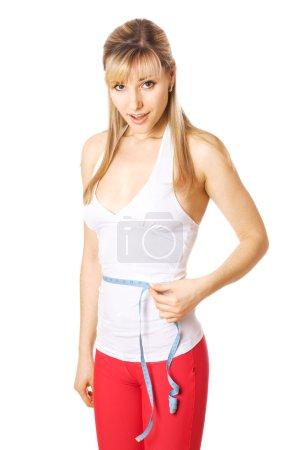 Blond woman measurin her waist size