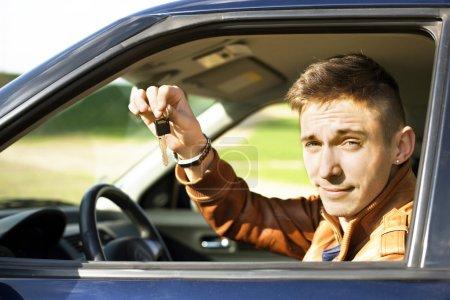 Photo pour Homme assis à l'intérieur de la voiture et montrant les clés de la nouvelle voiture - image libre de droit