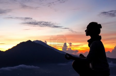 Photo for Silhouette of a girl that does yoga and meditation in the mountains at dawn. Stock image. - Royalty Free Image