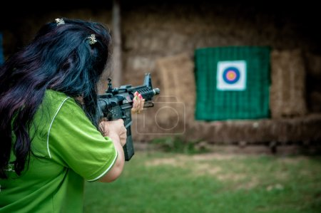 A young girl with a gun aiming at a target