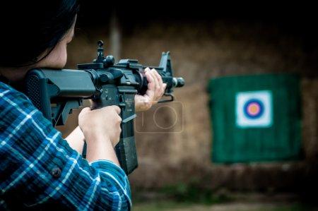 Photo pour Une jeune fille avec une arme visant une cible - image libre de droit