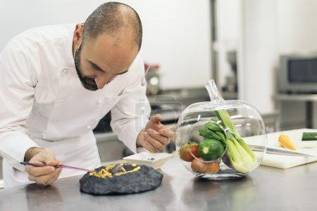 Photo pour Mâle chef professionnel cuisson dans une cuisine. - image libre de droit