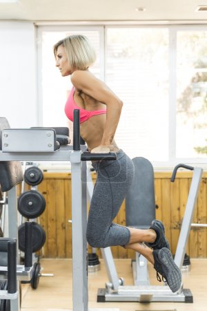 Young woman working triceps exercise at gym