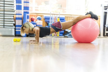 Pretty young woman doing exercises with a ball