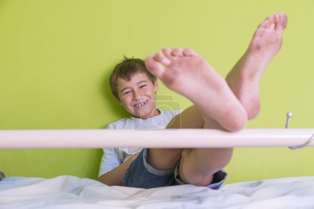 Photo for Little kid smiling with dirty feet and sitting at bed, posing on green background close-up - Royalty Free Image