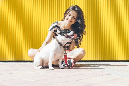 Happy woman are sitting with french bulldog