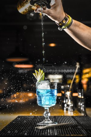 Photo for Barman pouring a cocktail into a glass at night club - Royalty Free Image