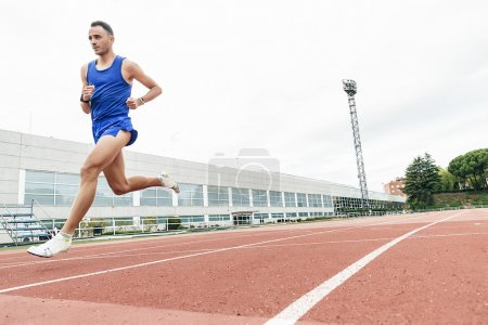 Attractive man Track Athlete Running On Track