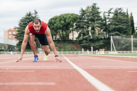 Photo for Man getting ready to start running on Stadium - Royalty Free Image