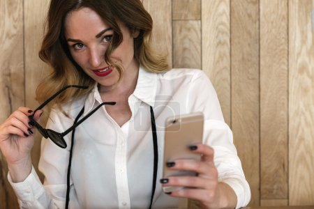 Elegant businesswoman writing text with a smartphone in a restau