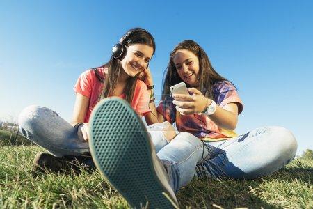 Happy teen friends in summer park listening music.