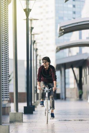 Photo pour Beau jeune homme à vélo dans la ville. Il est heureux. - image libre de droit