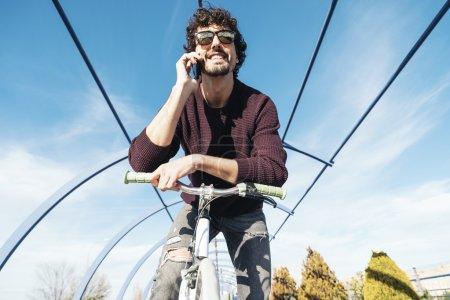 Photo pour Portrait d'un beau jeune homme avec téléphone portable et vélo à engrenages fixes dans la rue . - image libre de droit