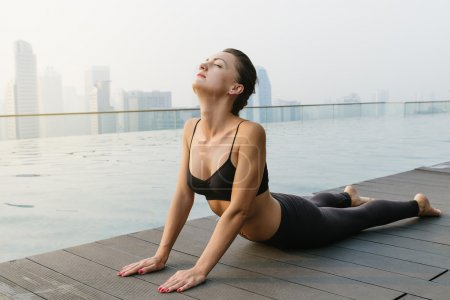 Relaxed young yoga woman in yoga pose near pool.