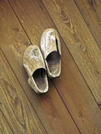 Old wooden clogs brown wall