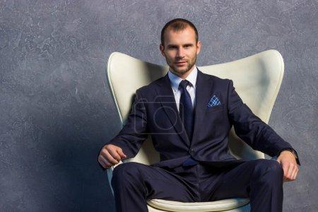 Photo pour Hommes d'affaires brutales en costume avec cravate, assis sur la chaise. Concept de boss. - image libre de droit