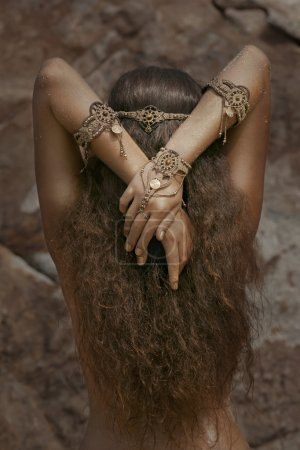 Girl in ethnic jewelry with mirror covered with sa...