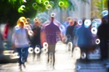 Photo pour Silhouettes brouillées des personnes marchant sur la rue contre le rétro-éclairage - image libre de droit