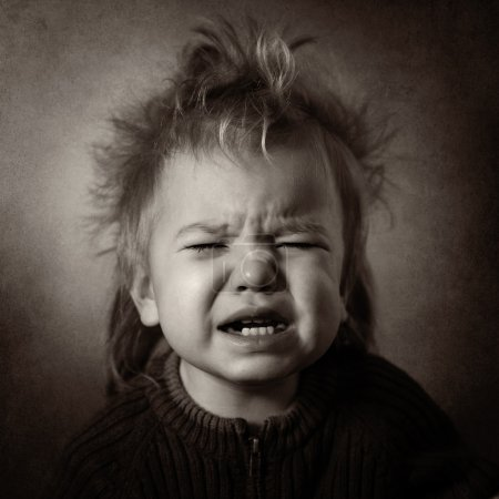 Photo for Monochrome portrait of a sobbing baby on a dark background - Royalty Free Image