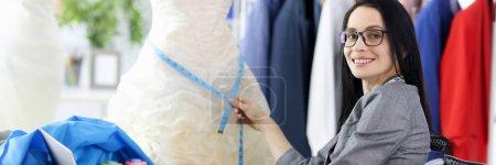 Photo pour Femme styliste en fauteuil roulant sur le lieu de travail. Concept de professions pour les personnes handicapées - image libre de droit