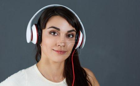 Photo pour Belle femme souriante aux cheveux bruns portant un casque, tenant le téléphone et écoutant de la musique sur fond gris. Concept de vie urbaine moderne - image libre de droit