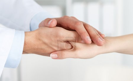 Friendly male doctor hands holding female patient hand