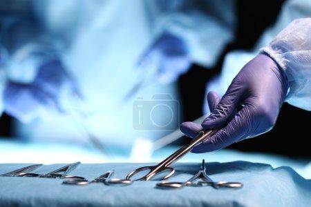 Nurse hand taking surgical instrument